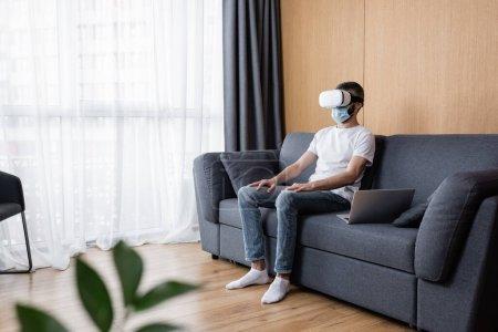 Selektiver Fokus des Mannes mit Kopfhörer und medizinischer Maske, der neben dem Laptop auf der Couch im Wohnzimmer sitzt