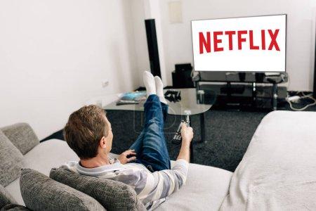 Photo pour KYIV, UKRAINE - 14 AVRIL 2020 : homme en jeans tenant la télécommande près de l'écran de télévision avec netflix à la maison - image libre de droit