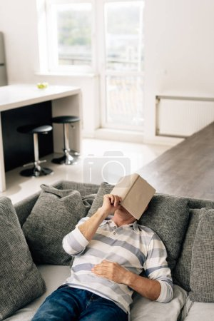 Photo for Man lying on sofa and touching book while covering face in living room - Royalty Free Image