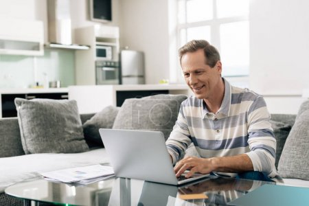 homme joyeux souriant tout en utilisant un ordinateur portable près de la carte de crédit dans le salon