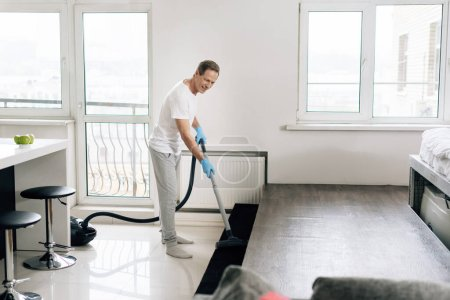 Photo for Selective focus of happy man cleaning apartment with vacuum cleaner - Royalty Free Image