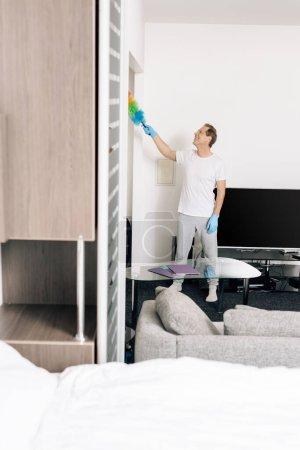 Photo pour Foyer sélectif de l'homme joyeux tenant brosse à poussière tout en nettoyant le salon - image libre de droit