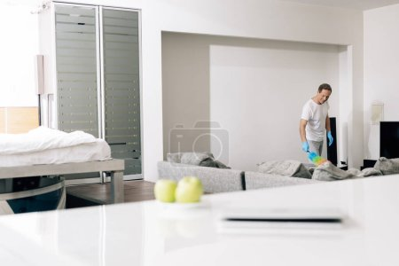 Photo for Selective focus of cheerful man holding duster brush while cleaning sofa in living room - Royalty Free Image