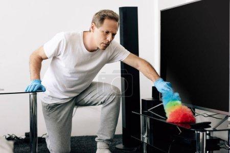 Photo pour Homme tenant brosse à poussière tout en nettoyant écran de télévision vierge dans le salon - image libre de droit