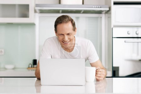 cheerful freelancer looking at laptop and holding cup at home