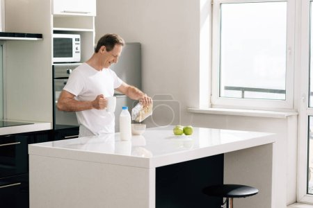happy man pouring cornflakes in bowl near bottle with milk and apples