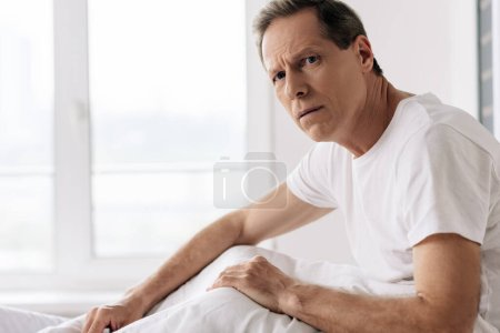 depressed man feeling unwell and looking at camera