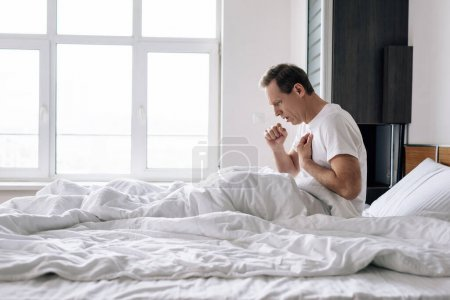 Photo for Side view of sick man coughing while sitting on bed at home - Royalty Free Image