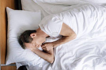 Photo pour Vue de dessus de l'homme malade toussant tout en étant couché sur le lit - image libre de droit