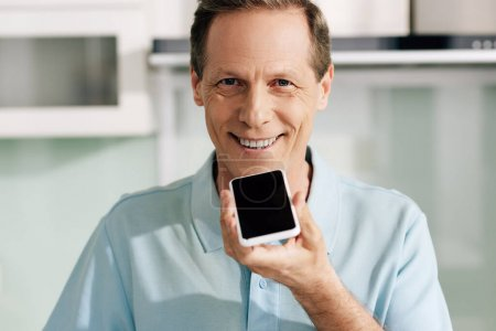 Photo for Happy man holding smartphone with blank screen while recording voice message - Royalty Free Image