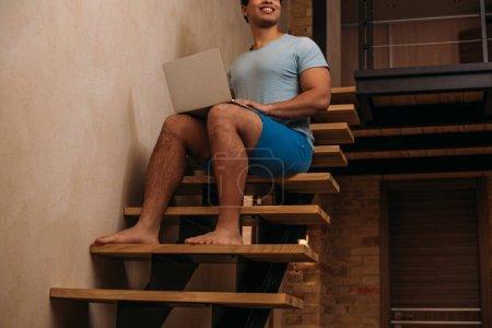 Photo pour Crosse d'un homme de race mixte utilisant un ordinateur portatif dans un escalier de la maison en quarantaine - image libre de droit