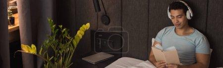 Photo pour Souriant mixte homme lecture livre tout en écoutant de la musique avec écouteurs au lit pendant la quarantaine, en-tête du site - image libre de droit