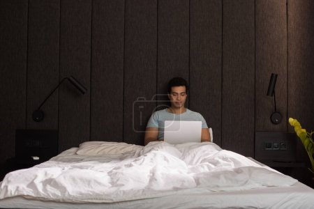 Photo for Male mixed race freelancer working on laptop in bed during self isolation - Royalty Free Image