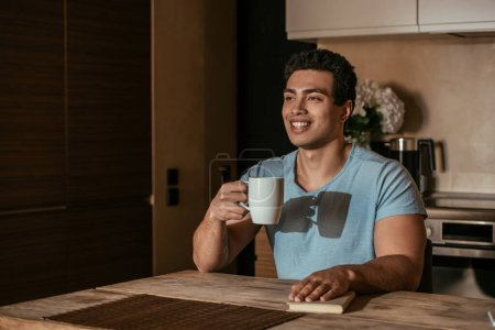 happy mixed race man holding cup of coffee and book on kitchen during quarantine