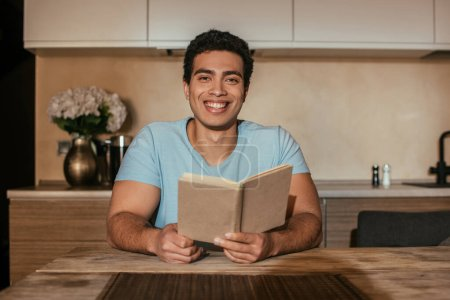 Photo for Smiling mixed race man reading book on kitchen during quarantine - Royalty Free Image