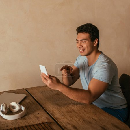 happy mixed race man pointing and having video call on smartphone at home on quarantine