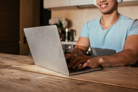abgeschnittene Ansicht eines lächelnden Mannes, der Musik mit Kopfhörern hört und Laptop während der Selbstisolation in der Küche benutzt