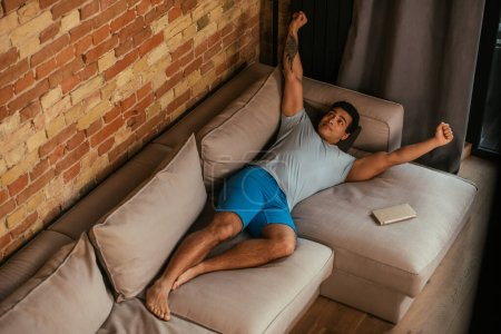 Photo for Handsome mixed race man stretching on sofa in living room during quarantine - Royalty Free Image