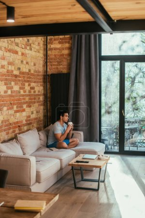 Photo for Handsome mixed race man holding cup of coffee on sofa in living room during quarantine - Royalty Free Image