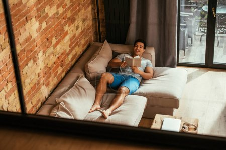mixed race man reading book while chilling on sofa during quarantine