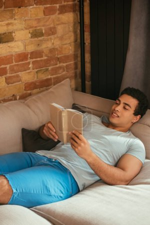 Photo for Handsome mixed race man reading book while chilling on sofa during self isolation - Royalty Free Image