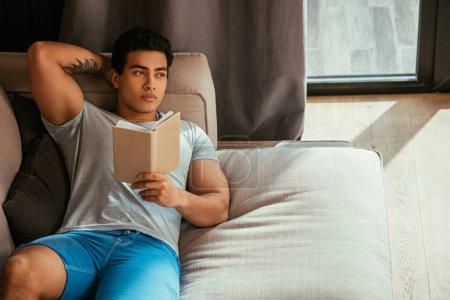 Photo pour Bel homme cher lisant le livre tout en se refroidissant sur le canapé pendant l'isolement personnel - image libre de droit