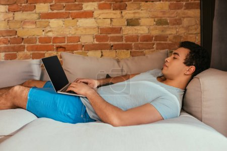sleepy mixed race man using laptop with blank screen on sofa at home on quarantine
