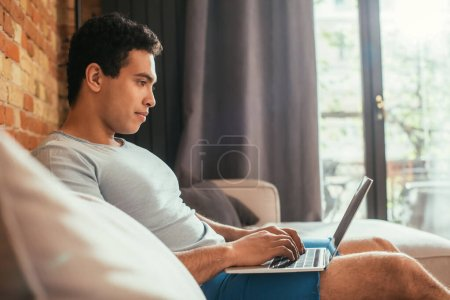 Photo for Happy young mixed race man chilling with laptop on sofa on quarantine - Royalty Free Image