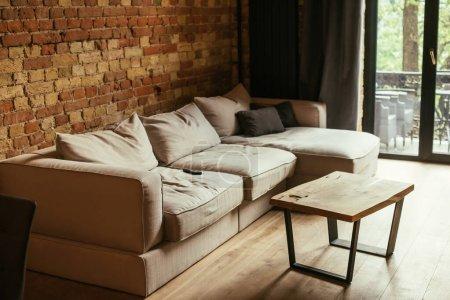 modernes Wohnzimmer mit beigem Sofa, Tisch und Fernbedienung