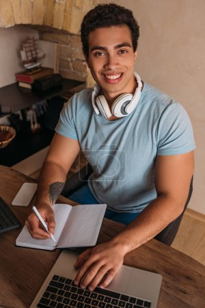 smiling mixed race freelancer working with laptop and notepad in home office during quarantine