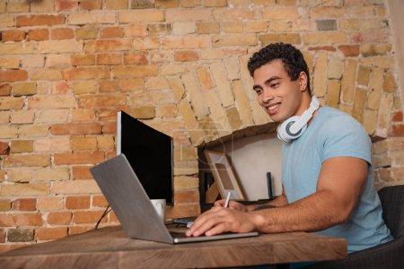 Photo pour Souriant mixte freelance travail avec ordinateur portable dans le bureau à la maison pendant l'isolement personnel - image libre de droit