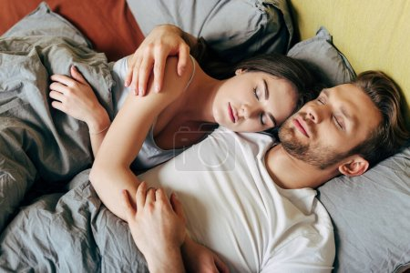 Photo for Overhead view of handsome man and attractive woman sleeping in bed - Royalty Free Image