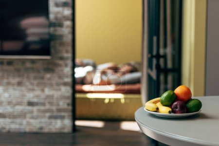 Photo for Selective focus of fresh and ripe fruits on table near couple in bedroom - Royalty Free Image