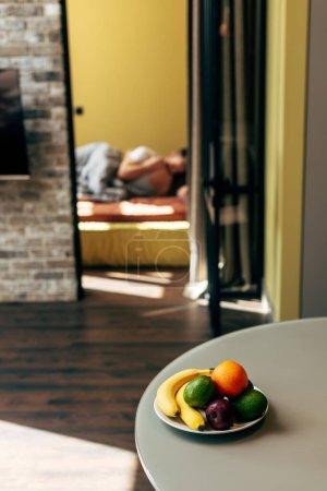selektiver Fokus von köstlichen Früchten auf dem Tisch in der Nähe von Paar im Schlafzimmer