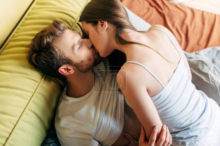 Photo for Overhead view of sexy couple kissing in bed - Royalty Free Image