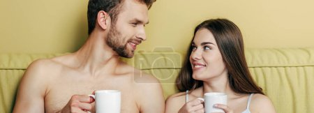 Photo for Horizontal image of happy couple looking at each other and holding cups with coffee - Royalty Free Image