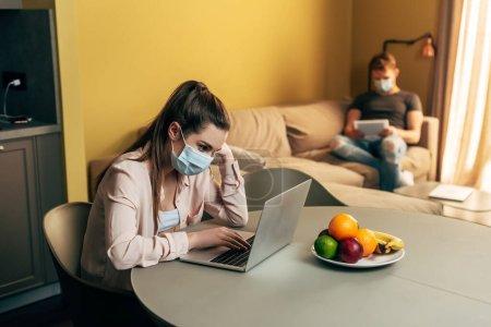Photo pour Foyer sélectif de pigiste dans le masque médical à l'aide d'un ordinateur portable près des fruits et l'homme avec tablette numérique à la maison - image libre de droit