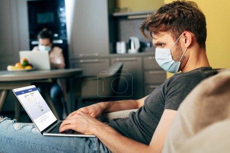 KIEW, UKRAINE - 22. April 2020: selektiver Fokus der Freiberuflerin in medizinischer Maske mittels Laptop mit Facebook-Website in der Nähe ihrer Freundin
