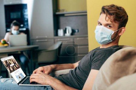 Photo pour KYIV, UKRAINE - 22 AVRIL 2020 : foyer sélectif de pigiste dans le masque médical à l'aide d'un ordinateur portable avec depositphotos site près de petite amie à la maison - image libre de droit
