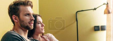 horizontales Bild eines bärtigen Mannes neben einer attraktiven Frau zu Hause