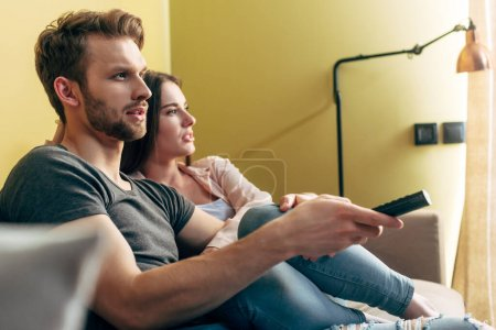 Selektive Fokussierung des bärtigen Mannes mit Fernbedienung und Filmschauen mit Freundin zu Hause
