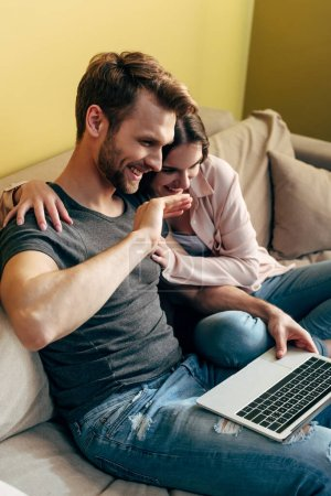 happy couple watching movie and laughing near laptop