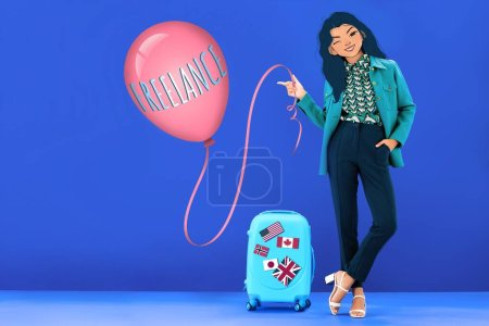 woman with illustrated face holding balloon with freelance lettering and standing near travel bag with flags on blue background
