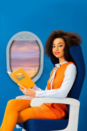 Photo for Smiling african american woman in retro dress holding book with dreams come true illustration while sitting on seat isolated on blue with porthole - Royalty Free Image