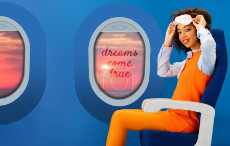 Photo for Smiling african american woman in orange retro dress holding sleeping mask and sitting on seat on blue background with portholes and dreams come true illustration - Royalty Free Image