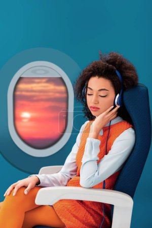 Photo for African american woman in retro dress listening to music and sleeping in seat on green background with sunset in porthole - Royalty Free Image