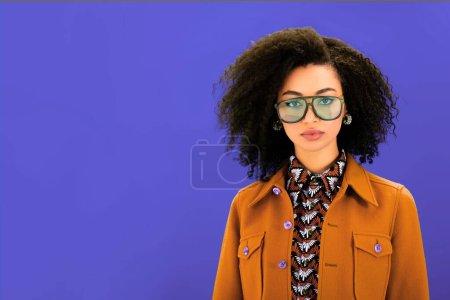 mujer afroamericana con estilo en chaqueta marrón mirando a la cámara aislada en púrpura