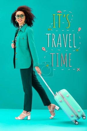 Photo for Smiling african american woman holding travel bag on turquoise background with it is travel time illustration - Royalty Free Image