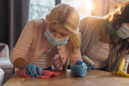 Photo pour Concentration sélective de la mère et de la fille dans les masques médicaux table de nettoyage dans le salon - image libre de droit