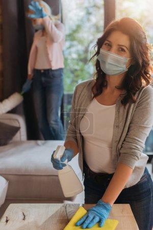 Photo pour Concentration sélective de la mère dans le masque médical tenant détergent et chiffon près de la fille avec brosse à poussière à la maison - image libre de droit